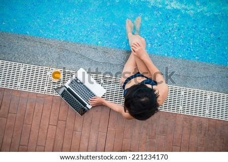 Woman sitting on the edge of the pool and using laptop, view from the top - stock photo