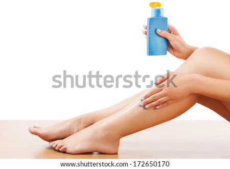 Woman sitting on the floor and apply body lotion on the leg skin.Studio shot - stock photo