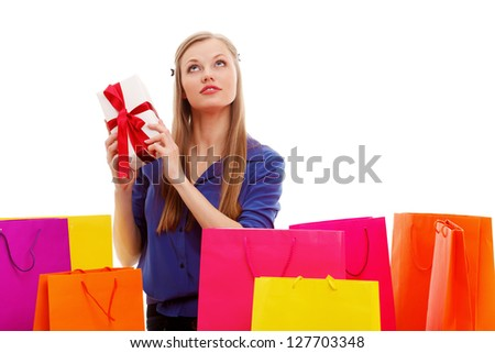 woman sitting on the floor behind shopping bags and holding gift box, isolated over white
