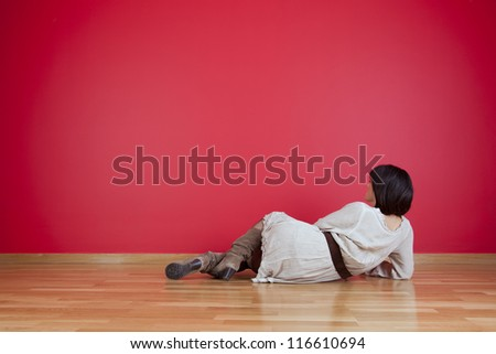 Woman sitting on the floor looking up to a red wall - stock photo