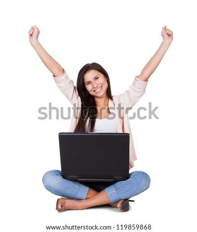 Woman sitting on the floor rejoicing with her laptop balanced on her lap and her arms raised in the air on a white background