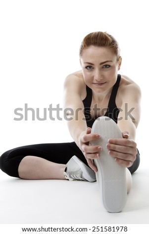 woman sitting on the floor stretching her legs - stock photo