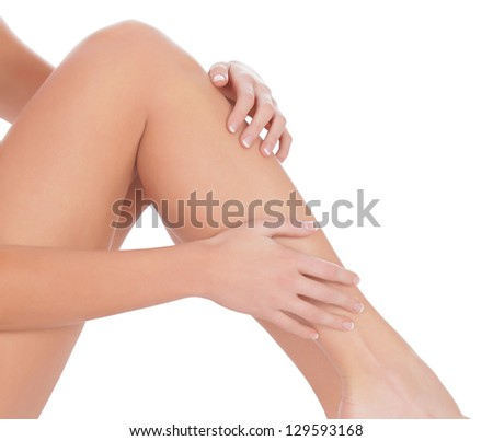 Woman sitting on the floor touch leg by hand, white background - stock photo
