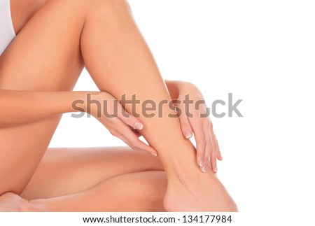 Woman sitting on the floor touches leg by hand, white background - stock photo