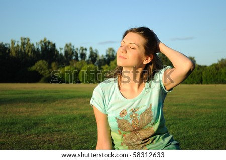 Woman sitting on the grass in park. - stock photo