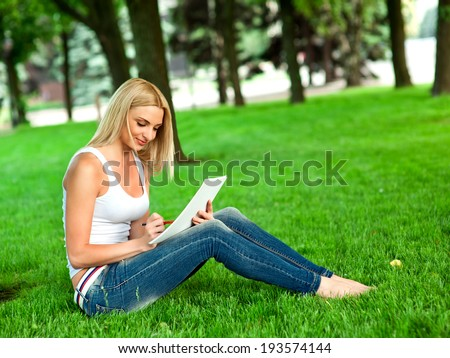 Woman sitting on the green grass and drawing