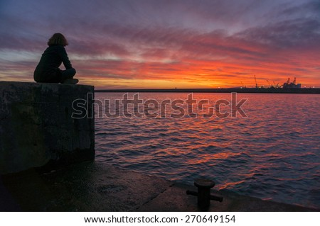 Woman sitting on the harbor watching the brightly colored sunset over the sea. - stock photo