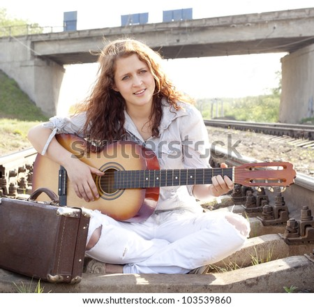 Woman sitting on the platform of a train station and singing and playing guitar  Hippie girl with an acoustic guitar and retro suitcase on the railway - stock photo