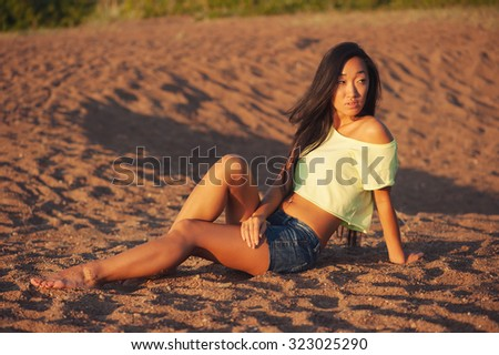 Woman sitting on the sand - stock photo