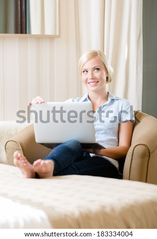 Woman sitting on the sofa with silver laptop. Concept of education and online communication