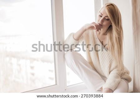 Woman sitting on the windowsill - stock photo