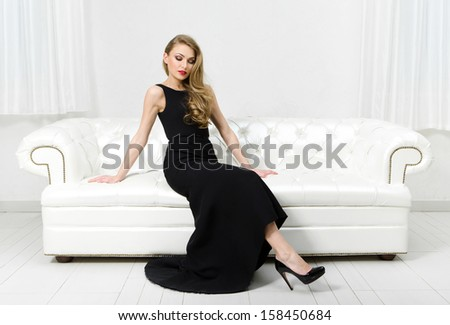 Woman sitting on white leather sofa. Concept of beauty and perfection - stock photo