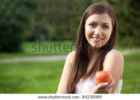 woman sitting on y\the grass and holding apple - stock photo