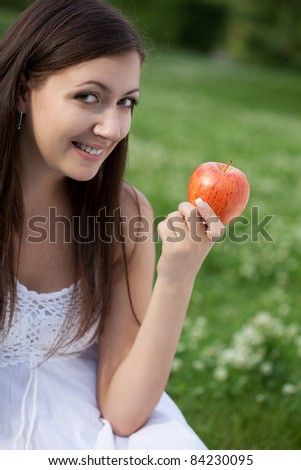 woman sitting on y\the grass and holding apple