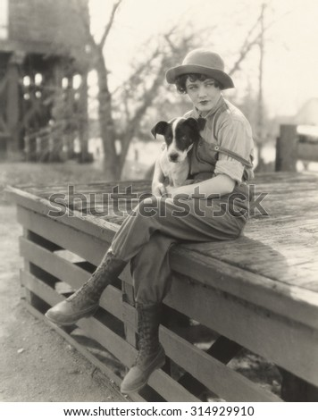 Woman sitting outdoors with her dog - stock photo