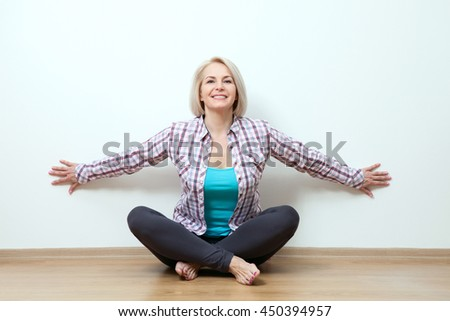 Woman sitting relaxed on the floor near a white wall