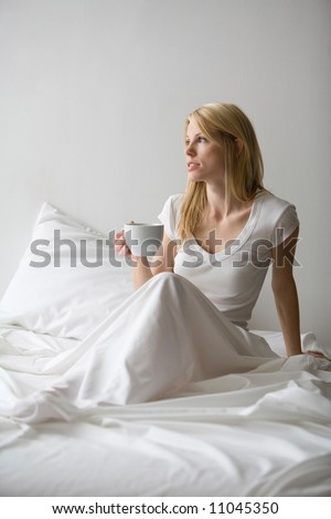 Woman sitting up in bed with white sheets and holding a cup of coffee - stock photo
