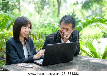 Woman sitting use computer in park - stock photo