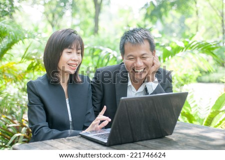 Woman sitting use computer on wooden table at home office ,background of green trees. - stock photo