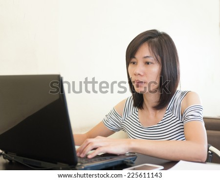 Woman sitting use computer on wooden table at home office ,background of green trees.