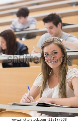 Woman sitting while smiling at the lecture hall and taking notes - stock photo
