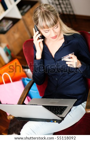 Woman sitting with a laptop in her home living room in front of a book shelf shopping or doing banking transactions online in the Internet, emphasized by shopping bags and her holding a credit card - stock photo