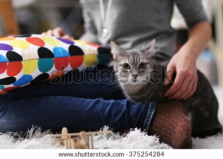 Woman sitting with cat on fur carpet at home - stock photo