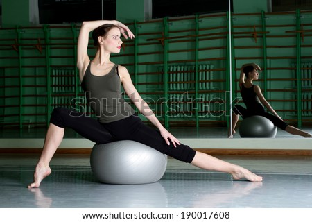 Woman sitting with exercise ball at dance hall - stock photo