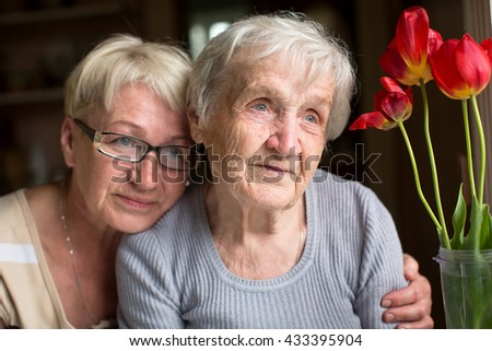 Woman sitting with her elderly mother. - stock photo
