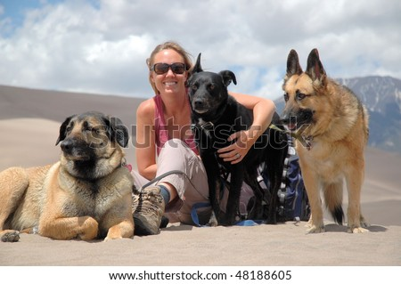 Woman sitting with three dogs - stock photo