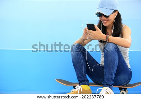 woman skateboarder listening music from smart phone mp3 player - stock photo