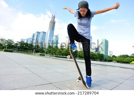 woman skateboarder skateboarding at city - stock photo