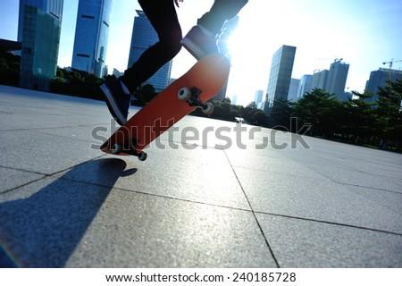 woman skateboarder skateboarding at sunrise city  - stock photo