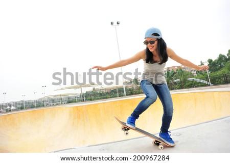 woman skateboarding at skatepark  - stock photo