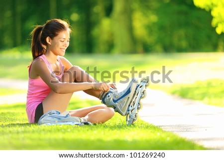 Woman skating in park. Girl going rollerblading sitting in grass putting on inline skates. Mixed race Asian Chinese / Caucasian woman in outdoor activities. - stock photo