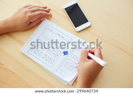Woman sketching on paper design new website - stock photo
