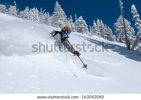 Woman skiing deep powder snow on a perfect winter day - stock photo
