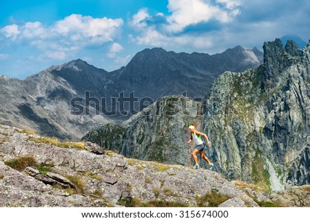 Woman skyrunner trains in the mountains - stock photo