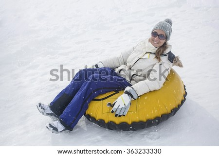 Woman sledding down a hill on a snow tube on a snowy day outdoors - stock photo