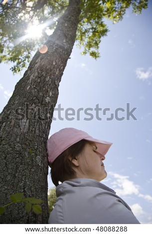woman sleeping against palm tree on sunny day - stock photo