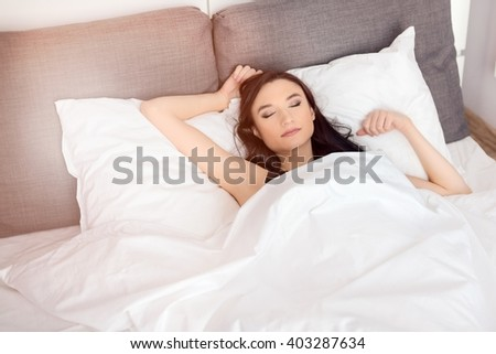 woman sleeping alone in her bed covered by white bedding. It is time to wake up