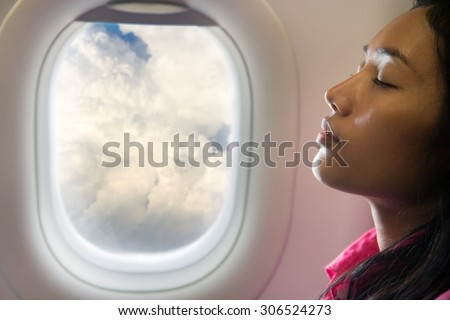 woman sleeping at air plane. Tired passenger resting at flying aircraft. Portrait of a sleeping woman dreaming in the clouds.