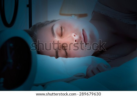 Woman sleeping in a bed with an alarm clock next to her in the dark - stock photo