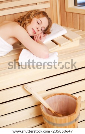 Woman sleeping in a sauna bath lying on her stomach on a wooden bench with her eyes closed with the water bucket and ladle in the foreground