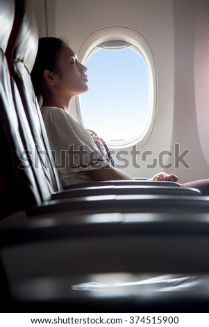 Woman sleeping in an airplane. Passenger in a flying aircraft sleep next to the window. Sleeping tired woman from a long airplane flight. Dreaming traveler on the plane beside a window with the blue. - stock photo