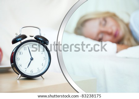 Woman sleeping in bed and alarm-clock (focus on alarm clock) Blank balloon with copyspace for your text and logo - stock photo