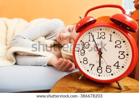 Woman sleeping in bed blanket with alarm clock. Girl relaxing napping in morning. Female about to wake up.