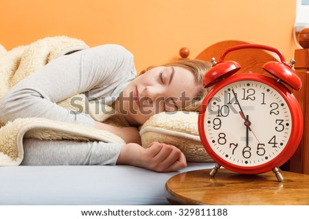 Woman sleeping in bed under wool blanket with set alarm clock. Girl relaxing napping in morning. Female about to wake up. - stock photo