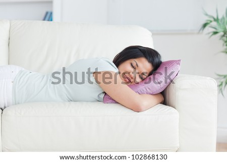 Woman sleeping on a couch with a pillow in a living room - stock photo