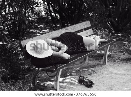 Woman sleeping on a desk on sunny day, dark sepia photo. Woman on siesta. Lunch time in Spain  - stock photo